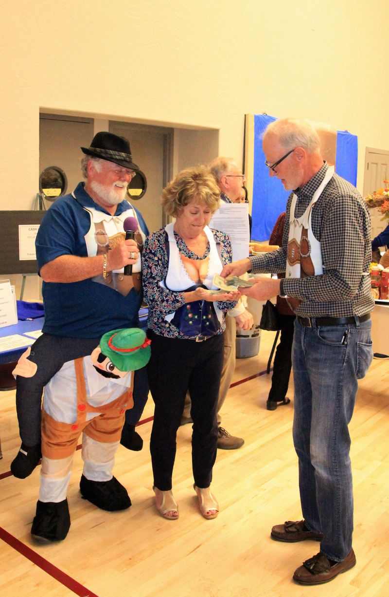 Club Youth Service Chair Dennis Bentley sells cash raffle tickets while MC Greg Crabtree counts the money.